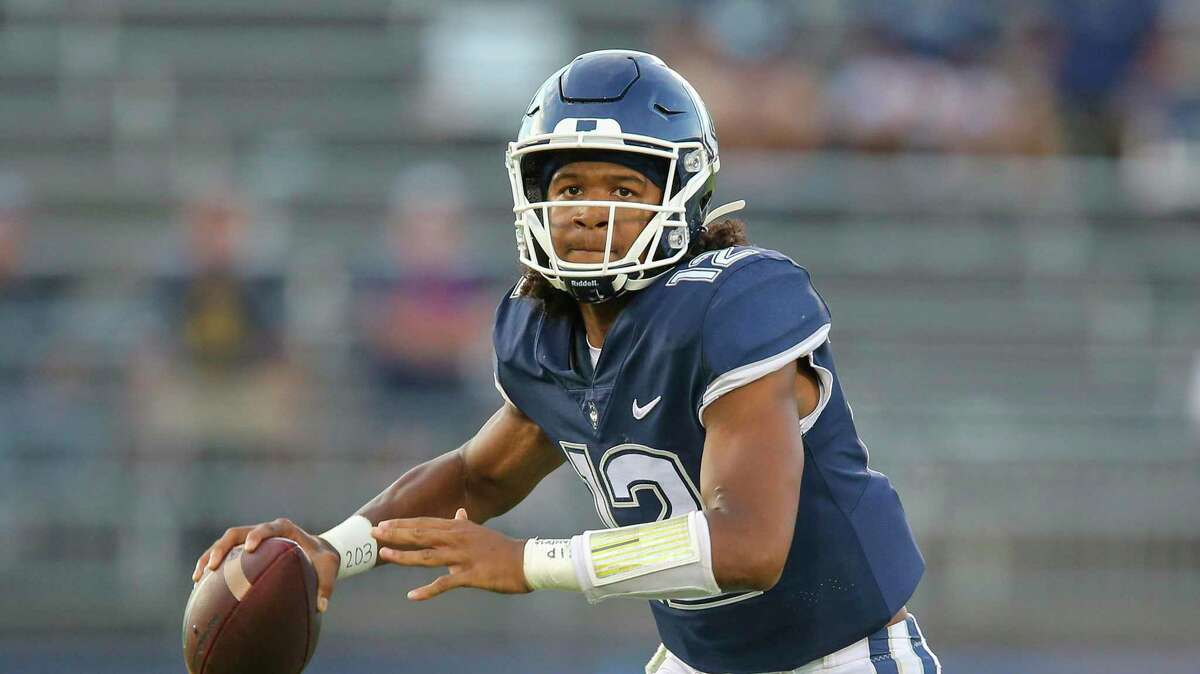 Connecticut quarterback Tyler Phommachanh (12) scrambles during the second half of an NCAA football game against Wyoming on Saturday, Sept. 25, 2021, in East Hartford, Conn. (AP Photo/Stew Milne)