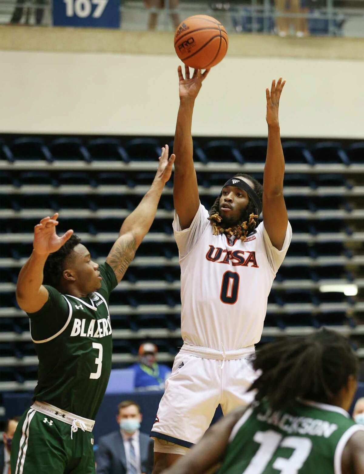 UTSA's Cedrick Alley Jr. (00) shoots over University of Alabama Birmingham's Tavin Lovan (03) during men's basketball at the Convocation Center on Friday, Feb. 26, 2021. UTSA goes down, 57-64, to UAB and will play again on Saturday.