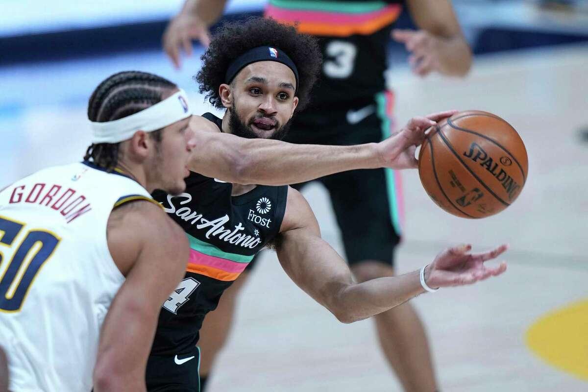 San Antonio Spurs guard Derrick White (4) passes around Denver Nuggets forward Aaron Gordon (50) during the second quarter of an NBA basketball game Wednesday, April 7, 2021, in Denver. (AP Photo/Jack Dempsey)