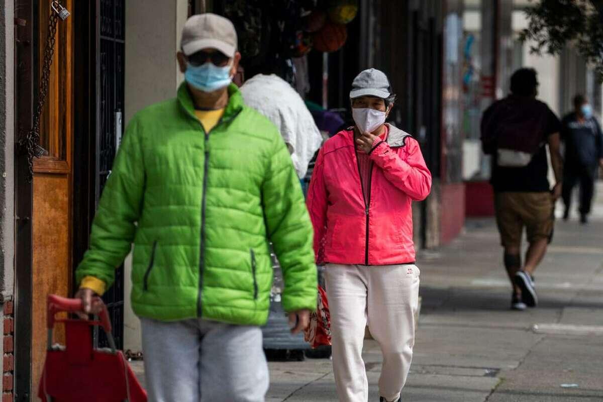 Masked pedestrians walk along Mission Street in the Excelsior District in San Francisco in April.