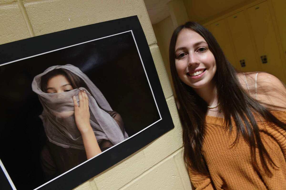 North Haven High School senior Zoey LoPresti is pictured on September 29, 2021 with a photograph she took as a sophomore of classmate, Aubrey Reyes, that won a Congressional Art Award and hangs in the Capitol Building in Washington D.C.
