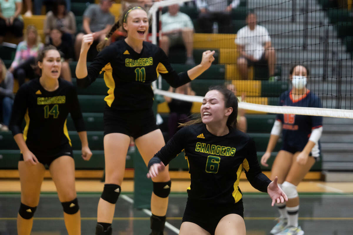 From left, Dow's Abby Rey, Summer Luick and Alex Price celebrate a point during the Chargers' match against Flint Powers Thursday, Sept. 30, 2021 at H. H. Dow High School. (Katy Kildee/kkildee@mdn.net)