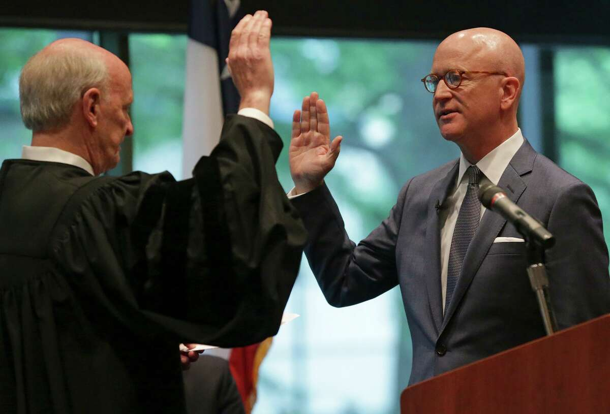 Robert Pitman is sworn in as a federal judge by Chief U.S. District Judge Fred Biery during an investiture ceremony at the Briscoe Western Art Museum on April 16, 2015.
