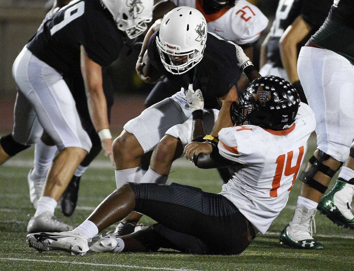 Kingwood Park quarterback Hayden Bender, top, is sacked by Texas City defensive end Szyron Scott (14) during the second half of a high school football game, Thursday, Sept. 30, 2021, in Humble.
