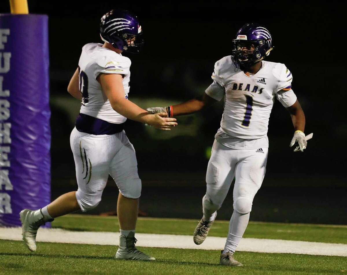 Montgomery offensive linemen Jaron Persky (70) gives running back Jalen Washington (1) a high-five after scoring a touchdown during the third quarter of a high school football game at Traylor Stadium, Thursday, Sept. 30, 2021, in Rosenberg.