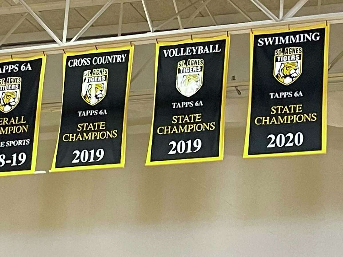 St. Agnes volleyball's 2019 state championship banner hangs in its gym among the school's many other state championship banners