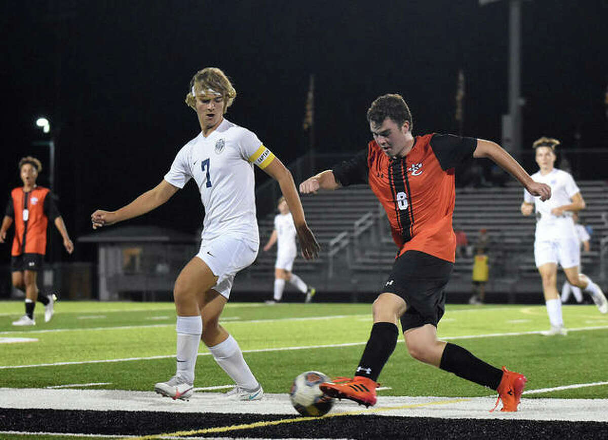 Edwardsville's George Windau shields the ball away from a defender as he dribbles up the field in the first half on Thursday against Belleville East.