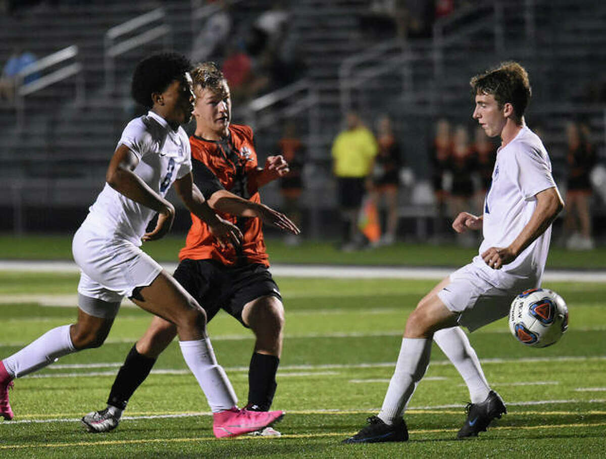 Edwardsville's Evan Moore blasts the game-winning goal past a pair of Belleville East defenders in the second overtime.
