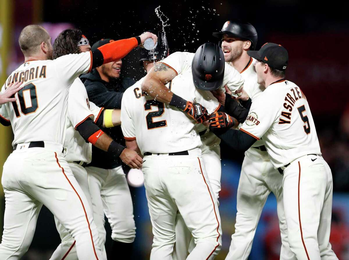 San Francisco Giants' LaMonte Wade, Jr. is mobbed by teammates after walk off hit giving Giants' 5-4 win over Arizona Diamondbacks during MLB game at Oracle Park in San Francisco, Calif., on Thursday, September 30, 2021.