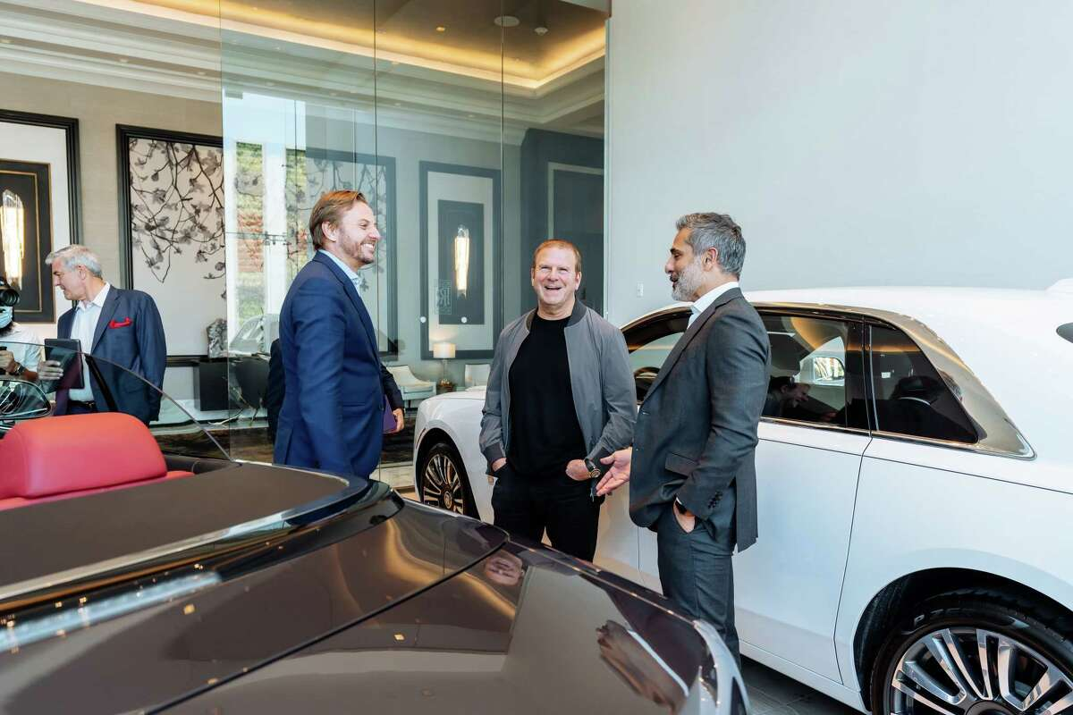 Tilman Fertitta poses with Martin Fritsches (left), president and CEO of Rolls-Royce Motor Americas and Lonny Soza (right), general manager of Rolls-Royce Motor Cars Houston, after the car manufacturer awarded Fertitta's Rolls-Royce Motor Cars Houston its North American Dealer of the Year award.