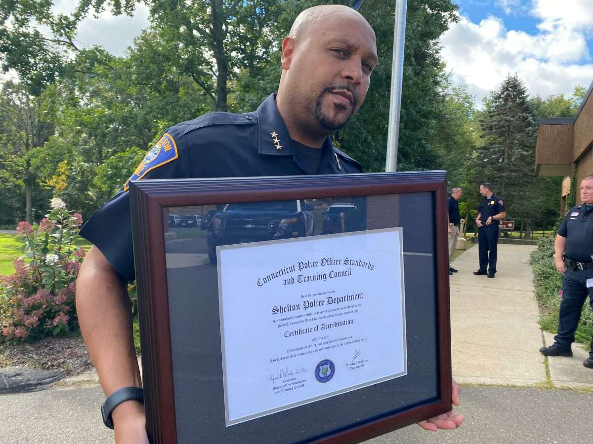 Shelton Police Chief Shawn Sequeira shows of the plaque recognizing the force has earned state Tier 1 reaccreditation.