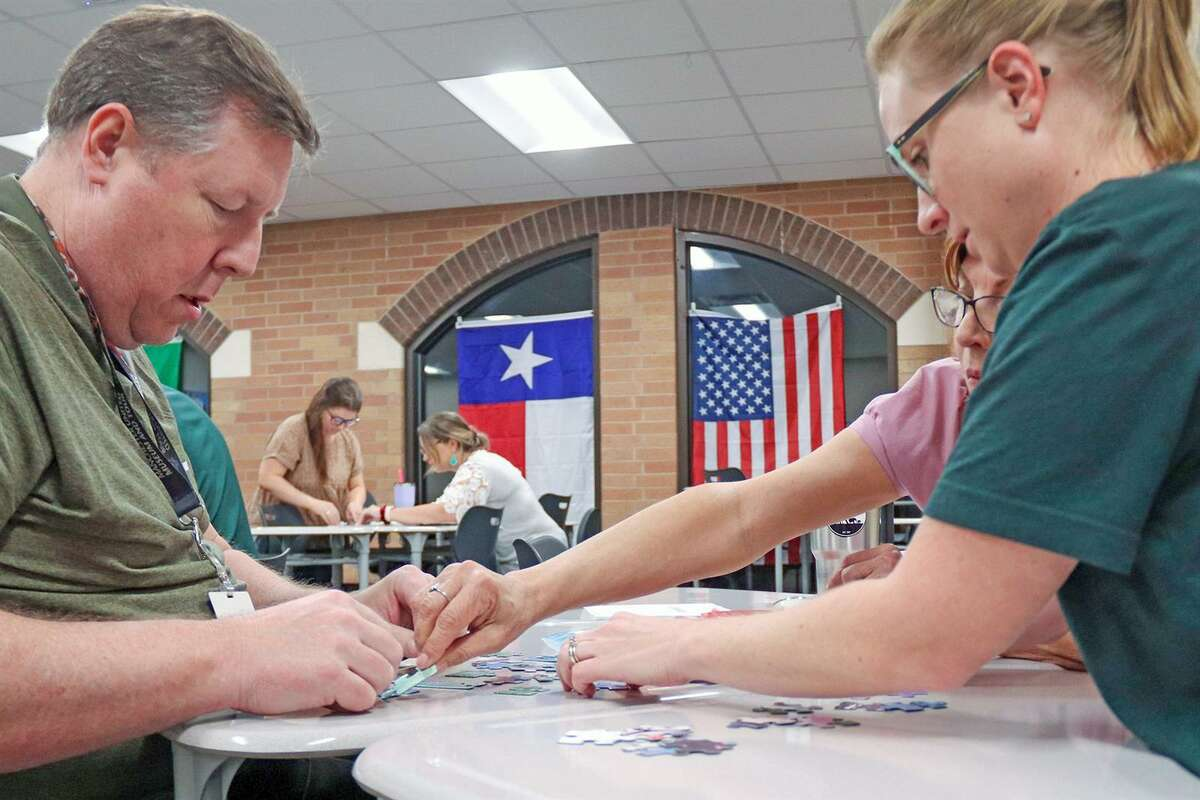 Cypress Falls High School Economics Teachers Dyce McCulloch, left, and Katy Vargas help put together a puzzle during the Social Studies Cup, a team competition created to bring teachers closer together. Teachers in content areas team together and compete in various events.