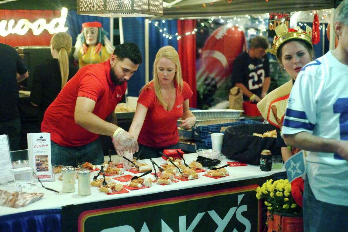 Holly Waters and Eli Rodriguez prepare taste samples at the Spanky's Pizza booth during the 2015 Taste of the Town.