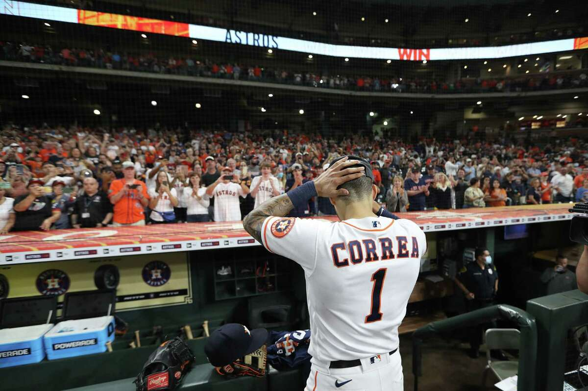Houston Astros shortstop Carlos Correa (1) takes off his jersey as the crowd cheered after Houston clinched the AL West with their 3-2 win over Tampa Bay Rays after an MLB baseball game at Minute Maid Park, Thursday, September 30, 2021, in Houston.