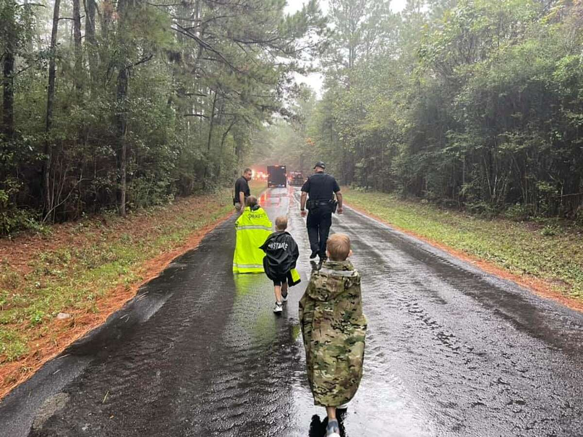 The three children found Friday morning in the Sam Houston National Forest after having gone missing there the night before can be seen walking through a road as escorted by first responders.