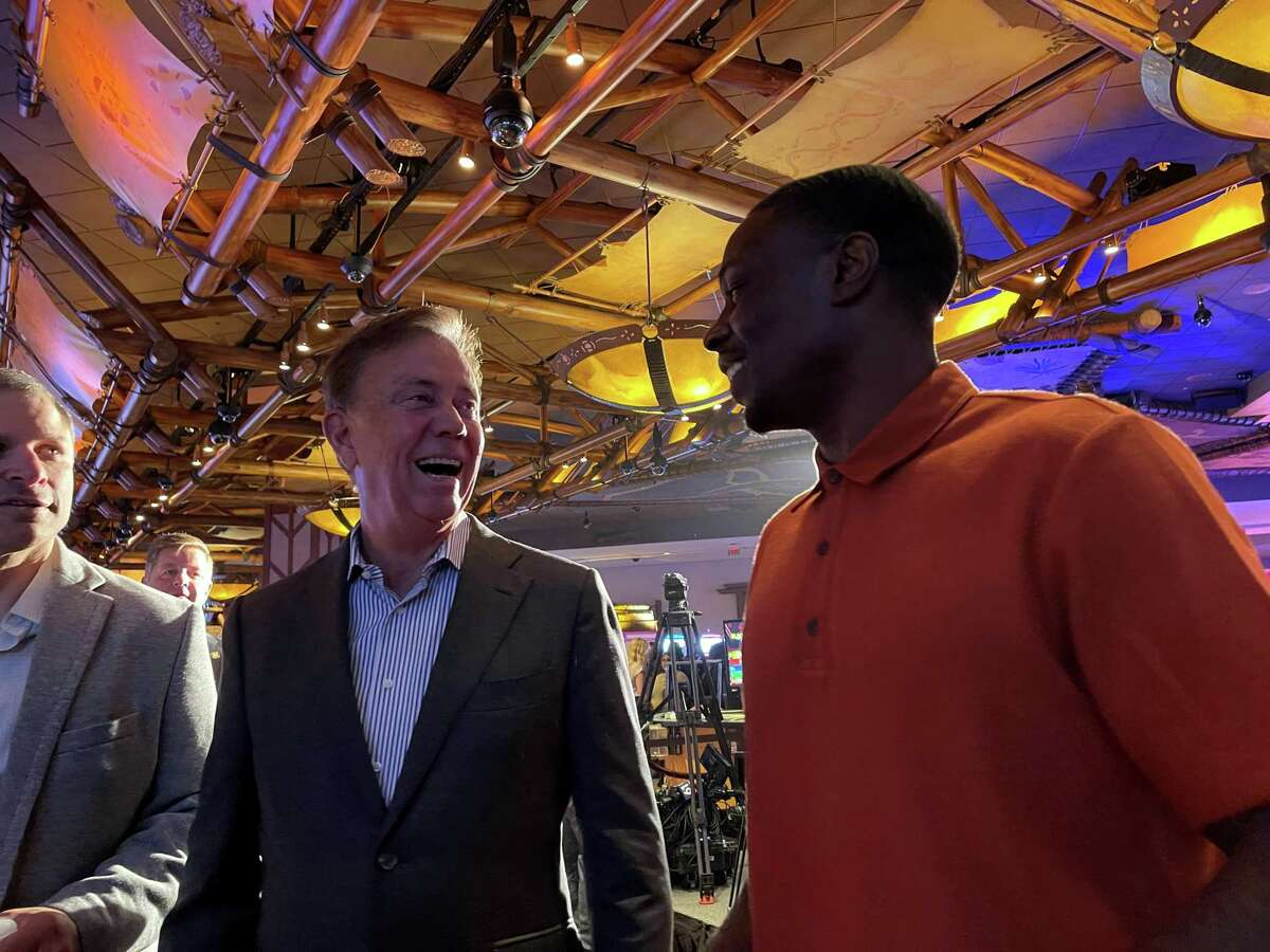 Gov. Ned Lamont talks to former UConn football player Darius Butler, who played nine years in the NFL, at Mohegan Sun casino Thursday morning.