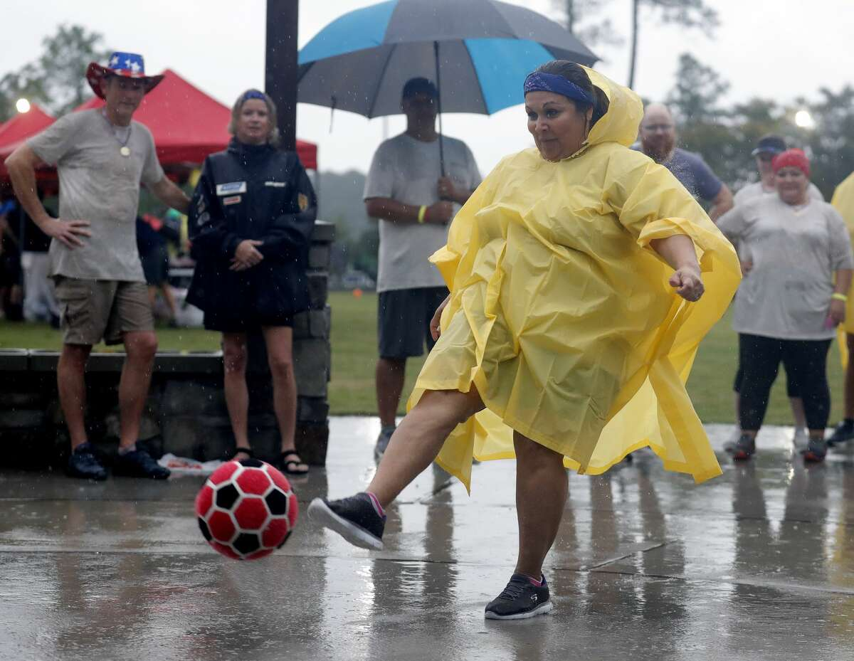 Cyndi Alvarado kicks a ball in the rain during YMCA's Dragon Boat Races at Northshore Park, Friday, Oct. 1, 2021, in The Woodlands. The annual event returned to The Woodlands on Thursday after a hiatus in 2020 due to the coronavirus pandemic.
