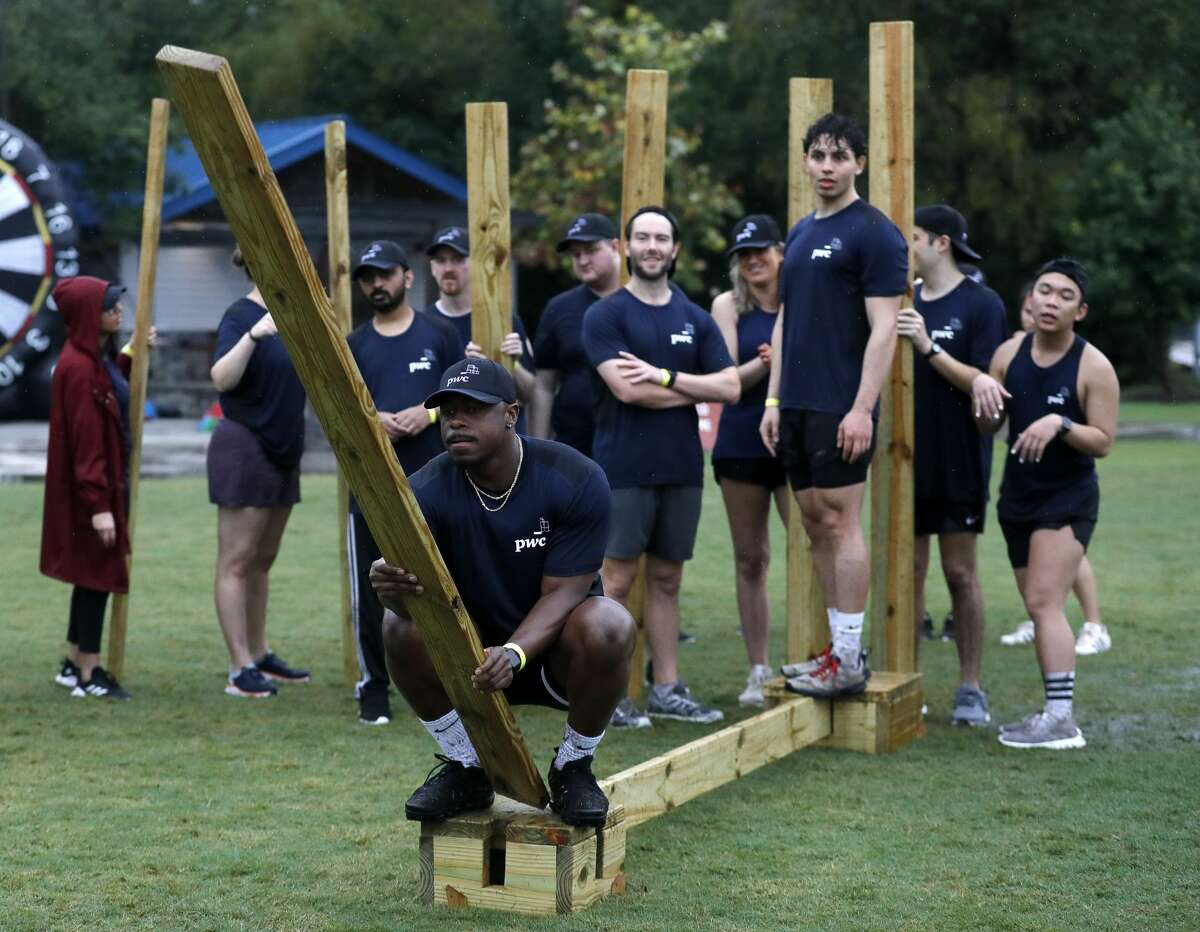 Ore Bankole places a board for his team to walk across during YMCA's Dragon Boat Races at Northshore Park, Friday, Oct. 1, 2021, in The Woodlands. The annual event returned to The Woodlands on Thursday after a hiatus in 2020 due to the coronavirus pandemic.