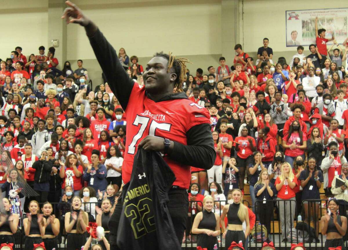 Kam Dewberry waves at the Atascocita crowd during the pep rally Friday in the Atascocita High School gym.