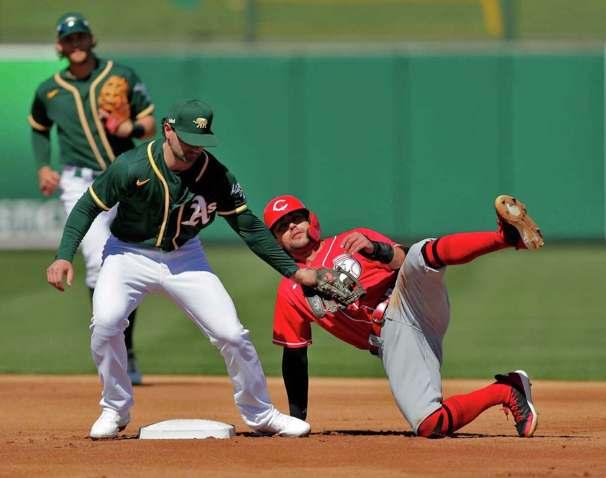 Alex Blandino (0) is tagged out by Pete Kozma (38) on a steal attempt in the first inning as the Oakland Athletics played the Cincinnati Reds at Hohokam Stadium in Mesa, Ariz., on Monday, March 1, 2021.