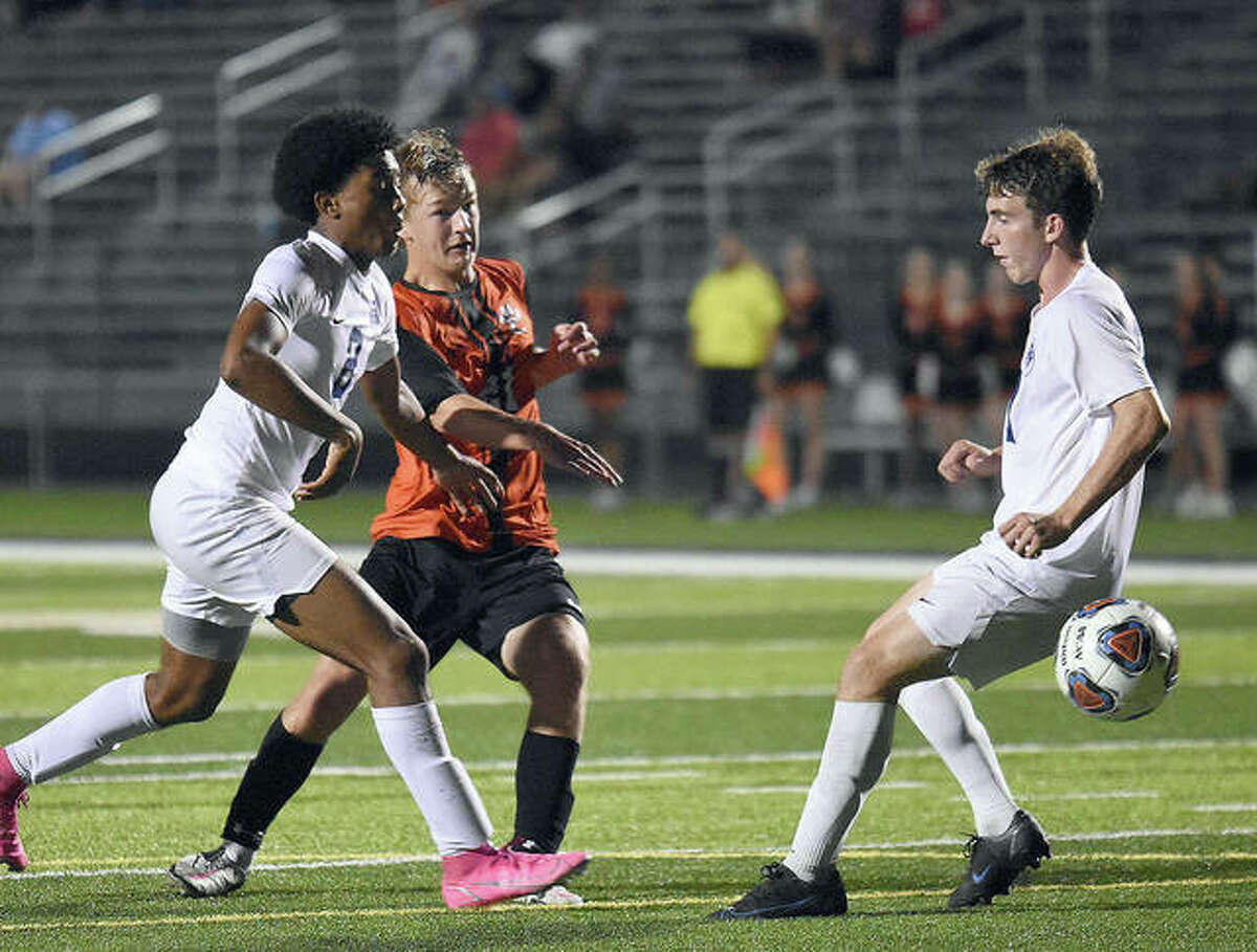 Edwardsville's Evan Moore blasts the game-winning goal past a pair of Belleville East defenders in the second overtime Thursday at the District 17 Sports Complex.