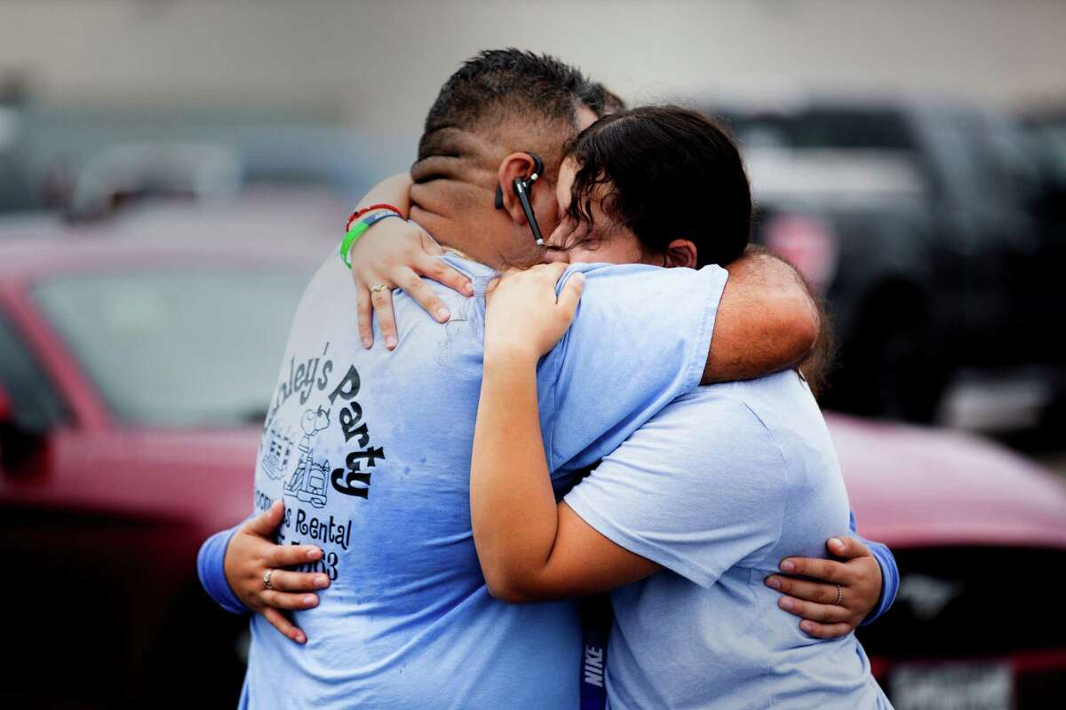 Yes Prep Southwest Secondary school student Kimberly Mendez, 14, embraces her father Rudis Méndez, 41, at a parking lot on the corner of Hiram Clarke Rd. and W. Fuqua St. after a shooting took place at her school, Friday, Oct. 1, 2021, in Houston.