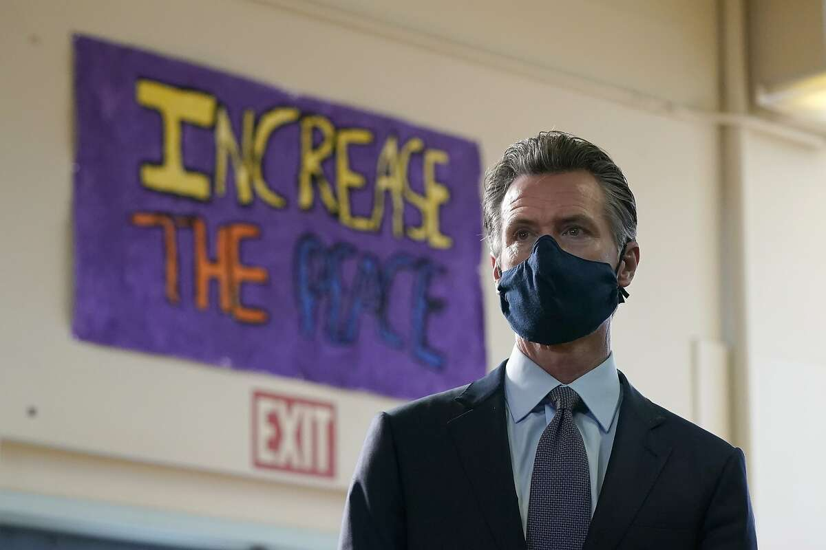 Gov. Gavin Newsom listens to speakers during a news conference at James Denman Middle School in San Francisco, Friday, Oct. 1, 2021. California has announced the nation's first coronavirus vaccine mandate for schoolchildren. Newsom said Friday that the mandate won't take effect until the COVID-19 vaccine has received final approval from the U.S. government for various grade levels. (AP Photo/Jeff Chiu)