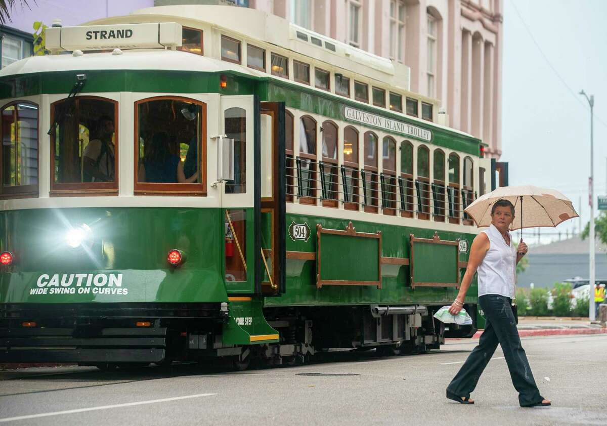 A woman walks by one of the new rail trolley cars on Postoffice Street, Friday, Oct. 1, 2021, in Galveston. The trolleys will be free to the public this weekend.