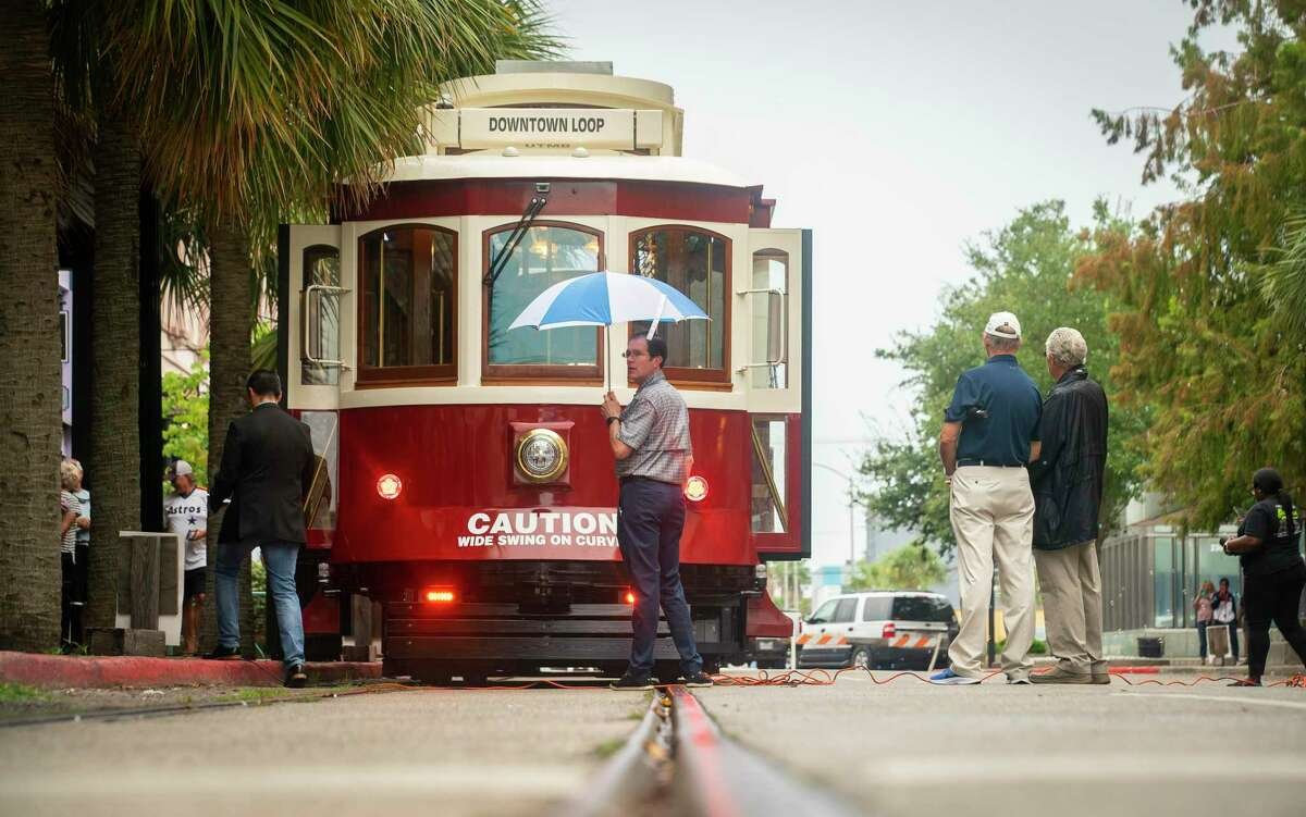 People wait for the start of a celebration for the new rail trolley cars on Postoffice Street, Friday, Oct. 1, 2021, in Galveston. The trolleys will be free to the public this weekend.