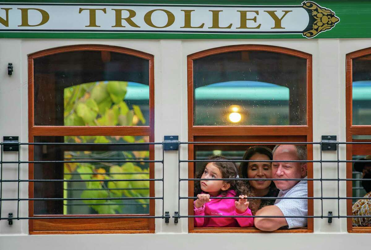 Casey Wright and his daughter, Abby, 5, look out of the window of one of the new rail trolley cars that is preparing to roll out on an inaugural trip following a celebration of the cars return to service, Friday, Oct. 1, 2021, in Galveston.