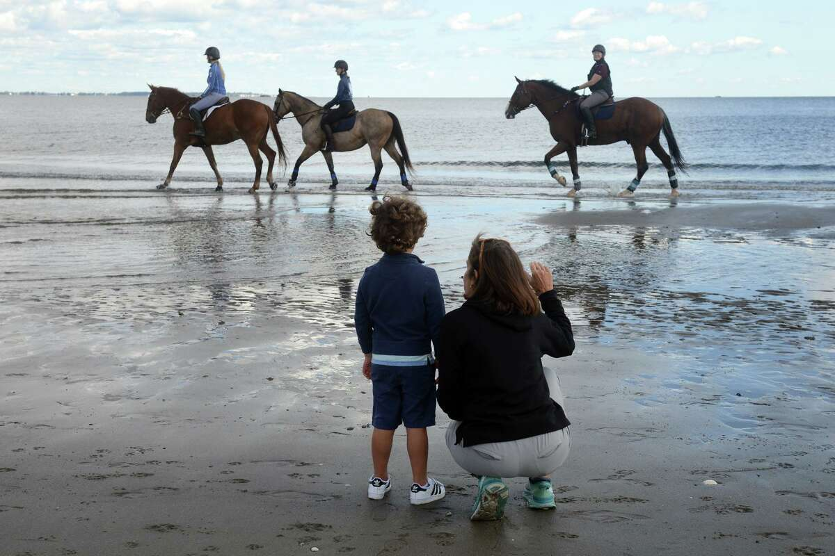 A woman and boy watch as a group of women ride on horseback at Penfield Beach, in Fairfield, Conn. Oct. 1, 2021.