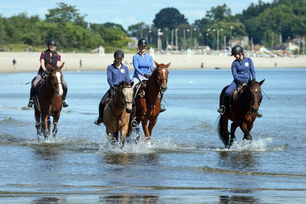 A group of women ride on horseback at Penfield Beach, in Fairfield, Conn. Oct. 1, 2021.