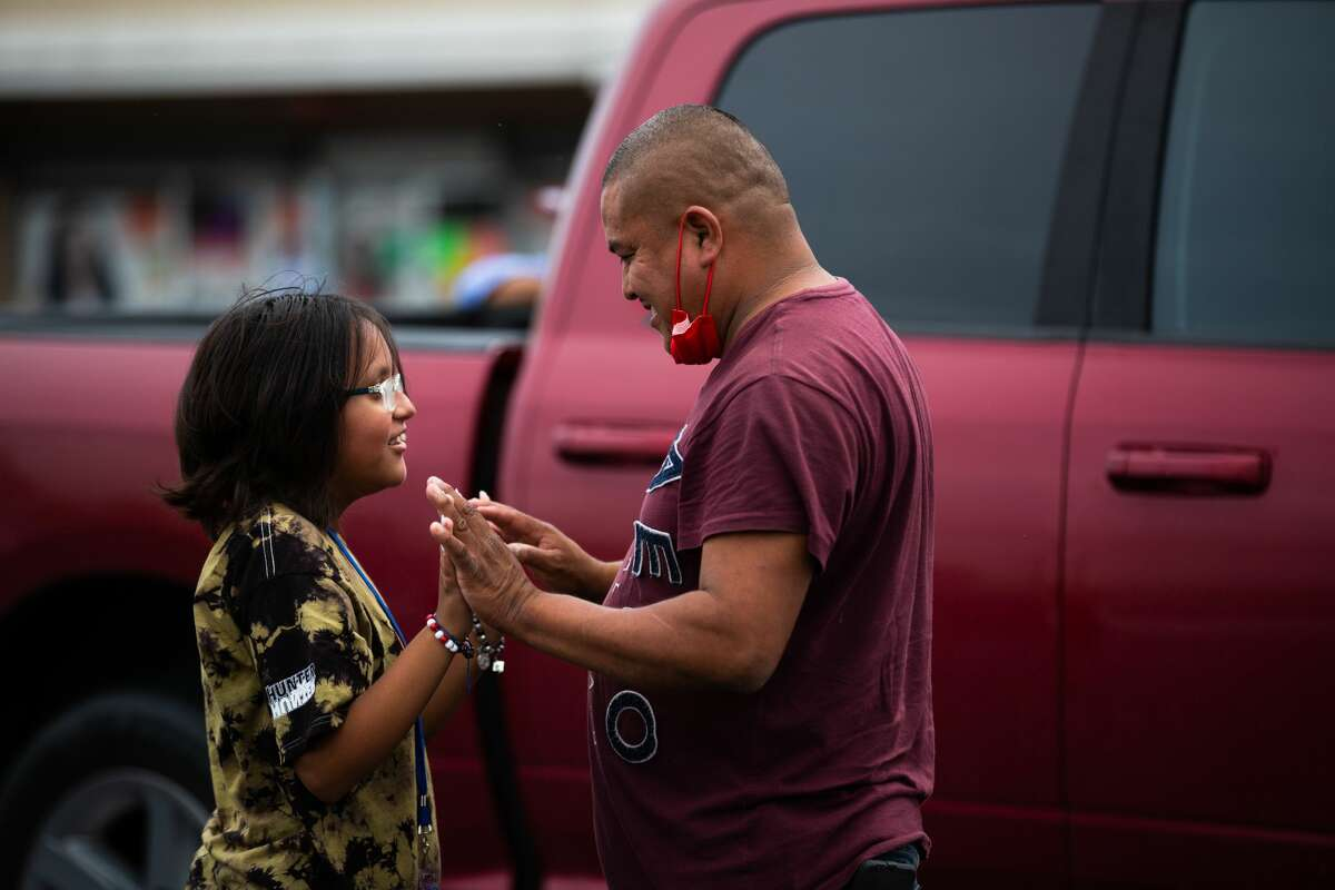 Homero Duque, 38, holds on to his daughter Melissa Duque, 11, who is a YES Prep Southwest Secondary school student as a school bus approaches to drop children at parking lot on the corner of Hiram Clarke Rd. and W. Fuqua St. after a shooting took place at the school, Friday, Oct. 1, 2021, in Houston. Melissa who is a sixth grader at the school was picked up from the school at 11:37 a.m. after calling her parents saying she felt uneasy, about 10 minutes before a report of an active shooter was reported. The pair went to the parking lot to try to meet up with Melissa's friends who where inside the school at the moment of the shooting because she got anxious about their safety.