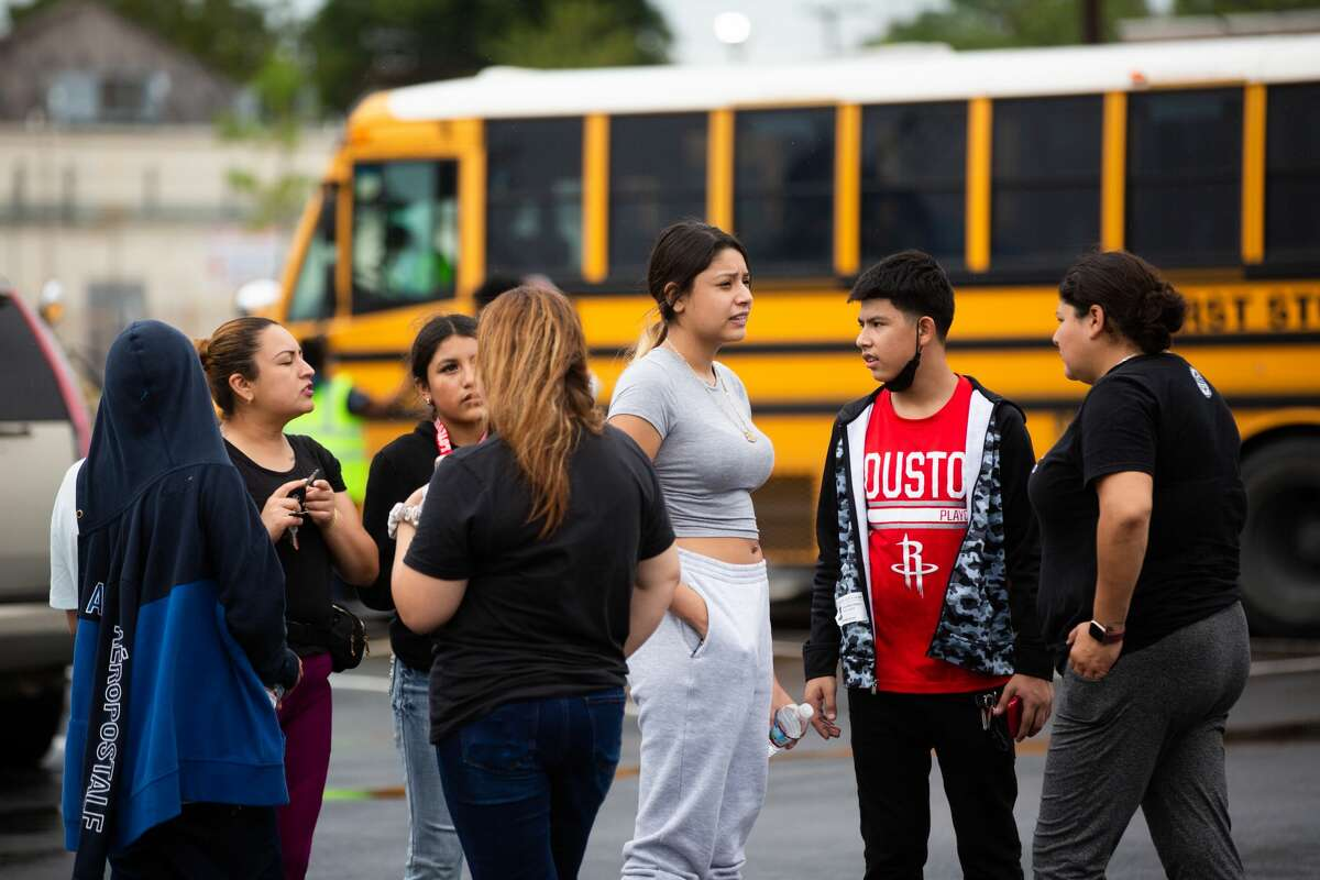 People wait at a parking lot on the corner of Hiram Clarke Rd. and W. Fuqua St. where families are meeting up with their children who study at YES Prep Southwest Secondary school after a shooting took place at the school, Friday, Oct. 1, 2021, in Houston.