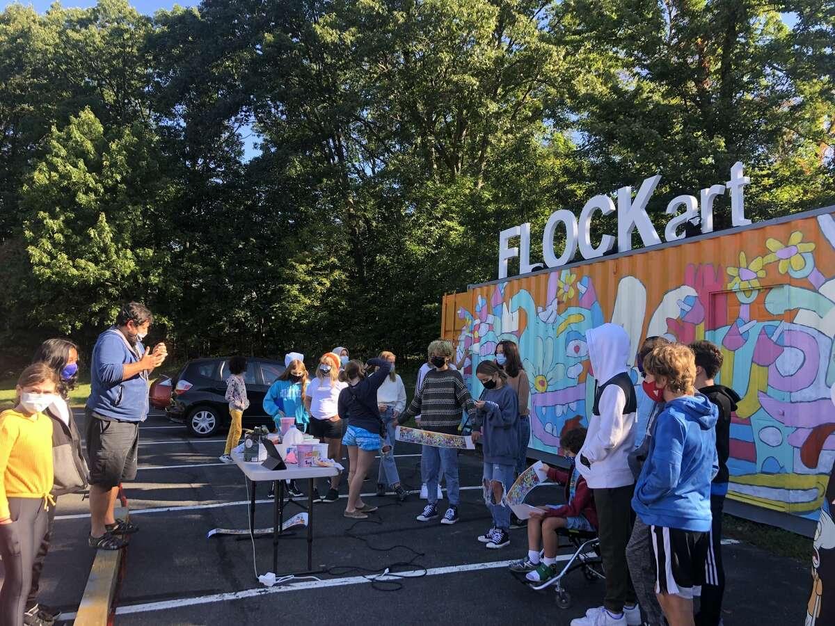 Students of Woodland Hill Montessori School in North Greenbush watch as artist Fernando Orellana paints the FLOCKart mural.