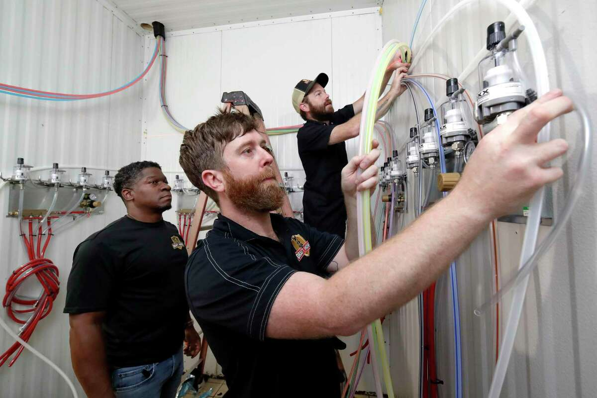 Lee Wagner, left, Lance Bridges and Aaron Hill with Draft Horse, a subsidiary of Charlie's Plumbing, install new beer lines Thursday into the keg cooling room as construction continues on the H-Town Restaurant and Sports Bar.