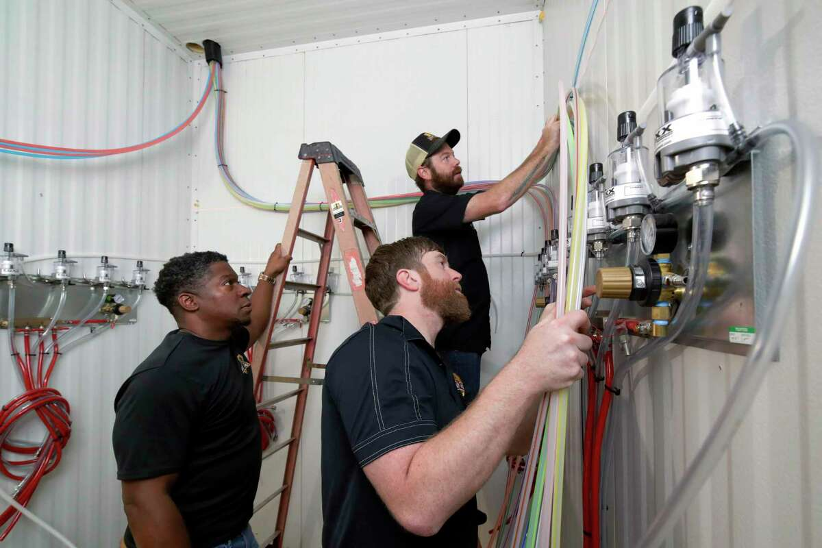 From left, Lee Wagner, Lance Bridges and Aaron Hill, with Draft Horse, a subsidiary of Charlies Plumbing that installs and maintains beer tap systems, run new beer lines into the keg cooling room as construction continues of the H-Town Restaurant and Sports Bar Thursday, Sep. 23, 2021 in Houston, TX.