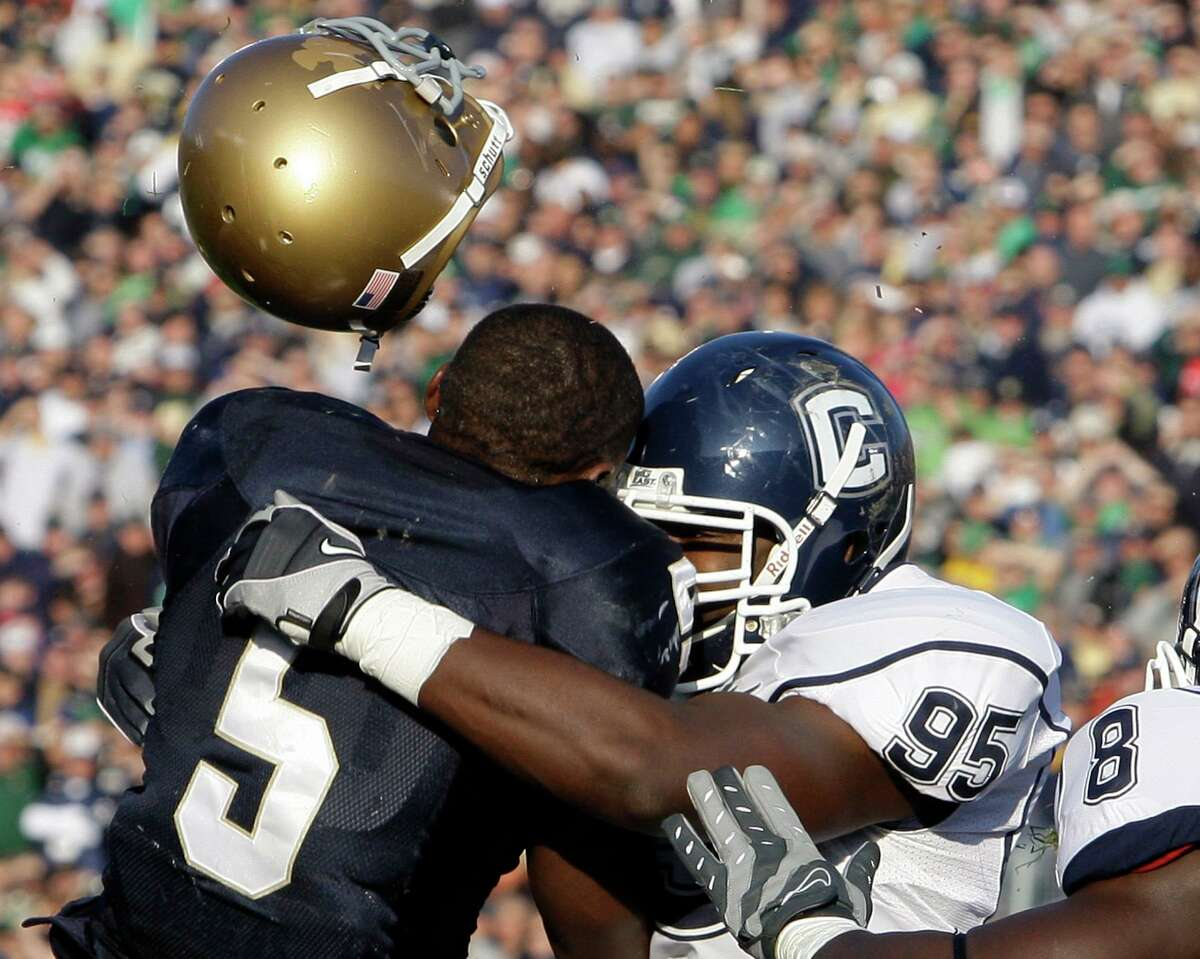 Notre Dame running back Armando Allen Jr., left, loses his helmet as he is hit by UConn linebacker Greg Lloyd during a 2009 game.
