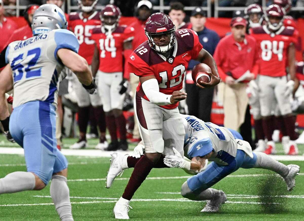 More than 400 Alliance of American Football players could receive unpaid wages under a settlement a bankruptcy judge gave preliminary approval to Friday. The league folded in April 2019 and entered bankruptcy. In this March 23, 2019 game at the Alamodome, San Antonio Commanders' Marquise Williams (12) evades Salt Lake Stallions' Cody Brown, right, and Josh Banderas.