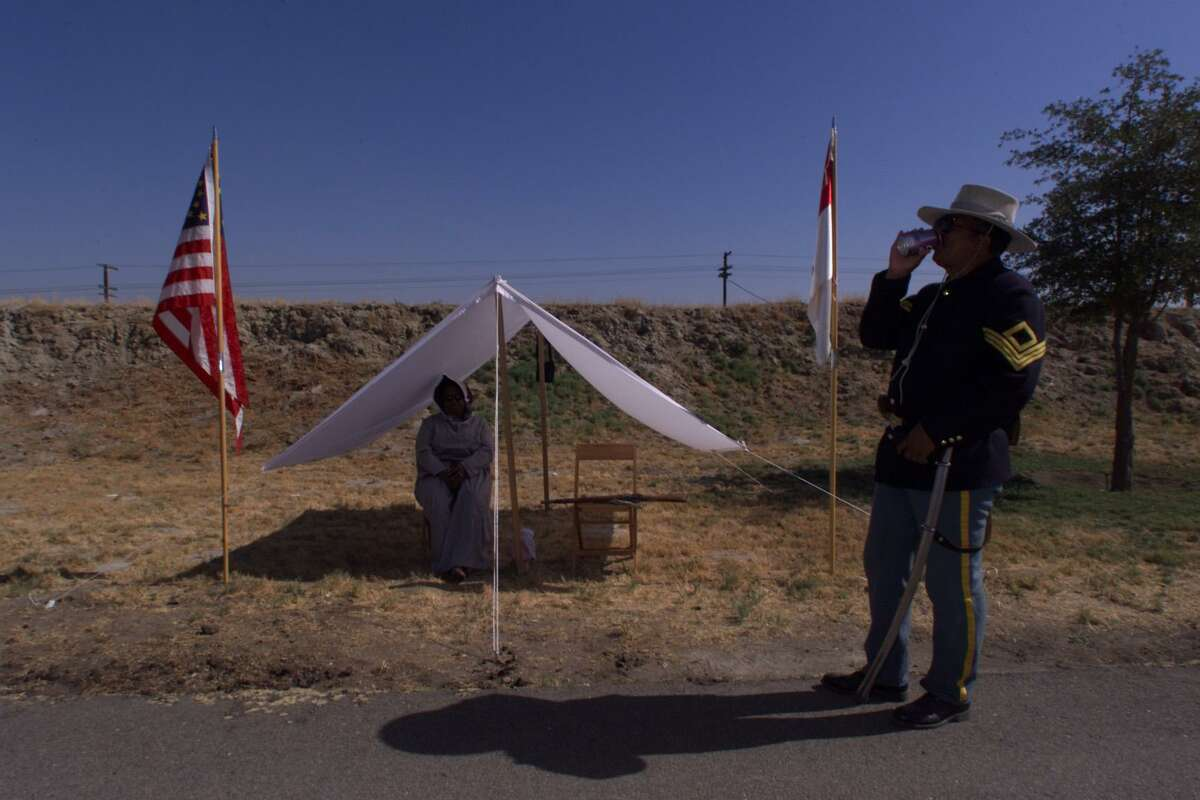 San Diego residents Johnnie Mitchell (center) and Troy Walker wait to greet participants in the 23rd annual rededication of Colonel Allensworth State Historic Park in Allensworth.