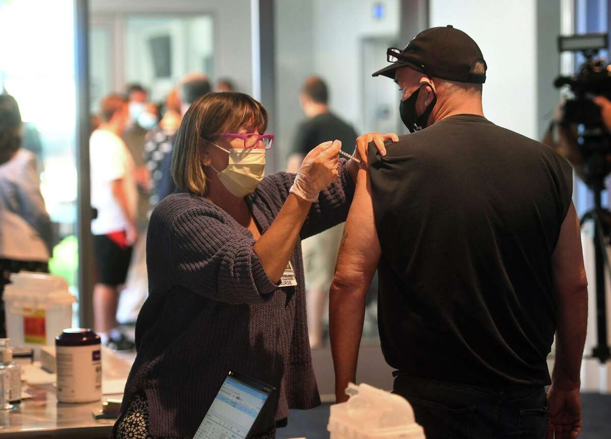 Janet Cordova, RN, gives the J&J Covid-19 vaccine to Breck Austin, of Newtown, at a free vaccination clinic at the Hartford Healthcare Amphitheater in Bridgeport, Conn. on Wednesday, August 25, 2021. Austin, who is a truck driver, said he was getting the vaccine at his girlfriend's insistence.