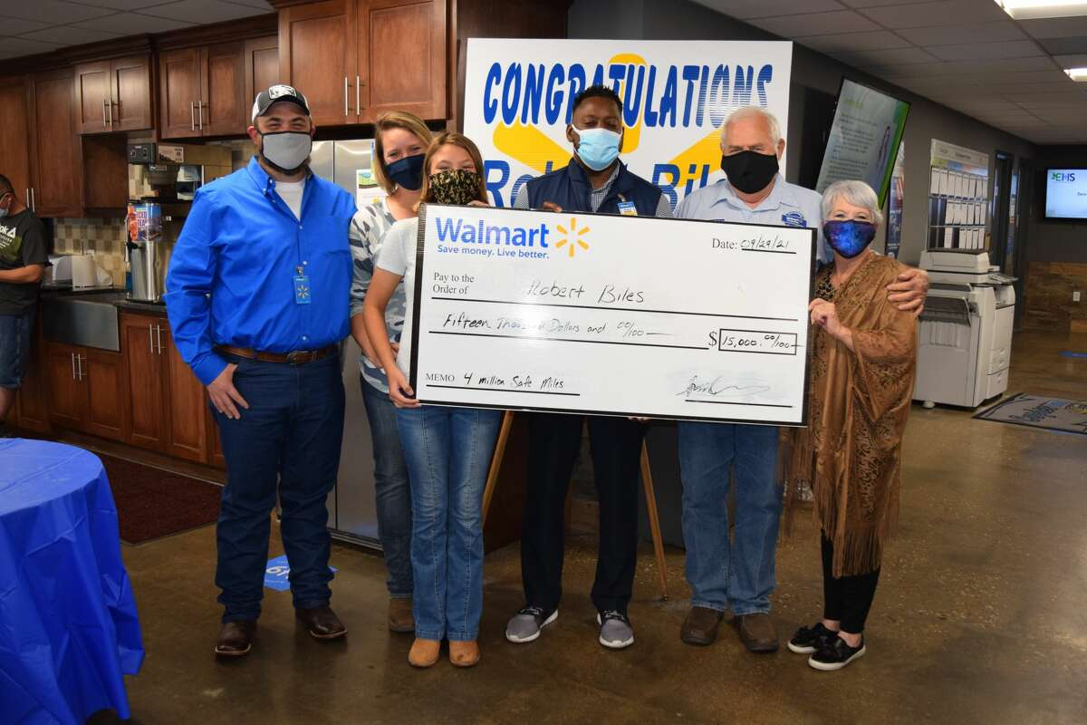 Robert Biles (right) and his family pose with a $15,000 reward check handed to him by Ronald James, general transportation manager for Walmart Distribution Center, for driving 4 million safe miles for Walmart Distribution. Pictured L-R: Cy Jackson, Becky Jackson, Shelby, Ronald James, Robert Biles and Sharon Biles