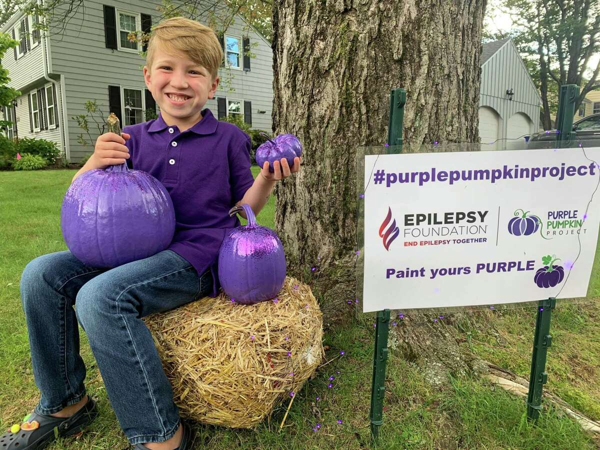Landon Heilbrunn, a six-year-old with epilepsy, sits outside his home with a few of the pumpkins they've already painted purple. The first grader is participating in the purple pumpkin project which raises money for the Epilepsy Foundation.