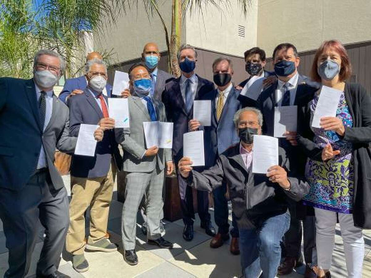 A mostly male crowd attends Gov. Gavin Newsom's signing of a package of affordable housing bills at the Coliseum Connections apartment complex in Oakland last month.