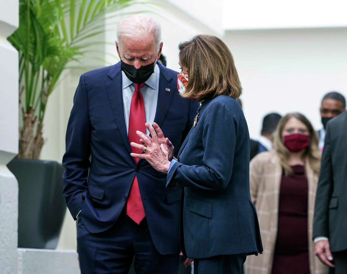 President Joe Biden talks with House Speaker Nancy Pelosi, D-Calif., as they leave a caucus meeting Friday. Biden called the meeting in order to push through an impasse with his infrastructure plan.