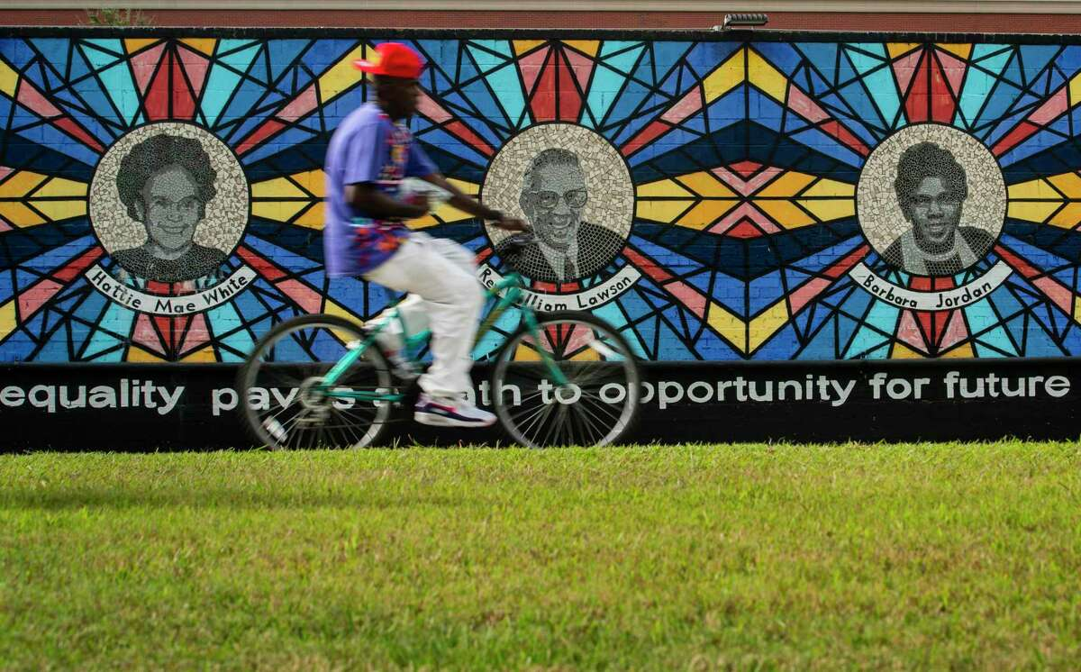 """A cyclist travels north up the Columbia Tap Rail-Trail past the """"Sacred Struggles/Vibrant Justice"""" mural honoring Houston civil rights leaders, Thursday, Sept. 30, 2021, just south of Texas Southern University in Houston. U.S. Rep. Sheila Jackson Lee would lose downtown and the entire Third Ward area if a proposed redrawn District 18 map is accepted by the current legislature."""