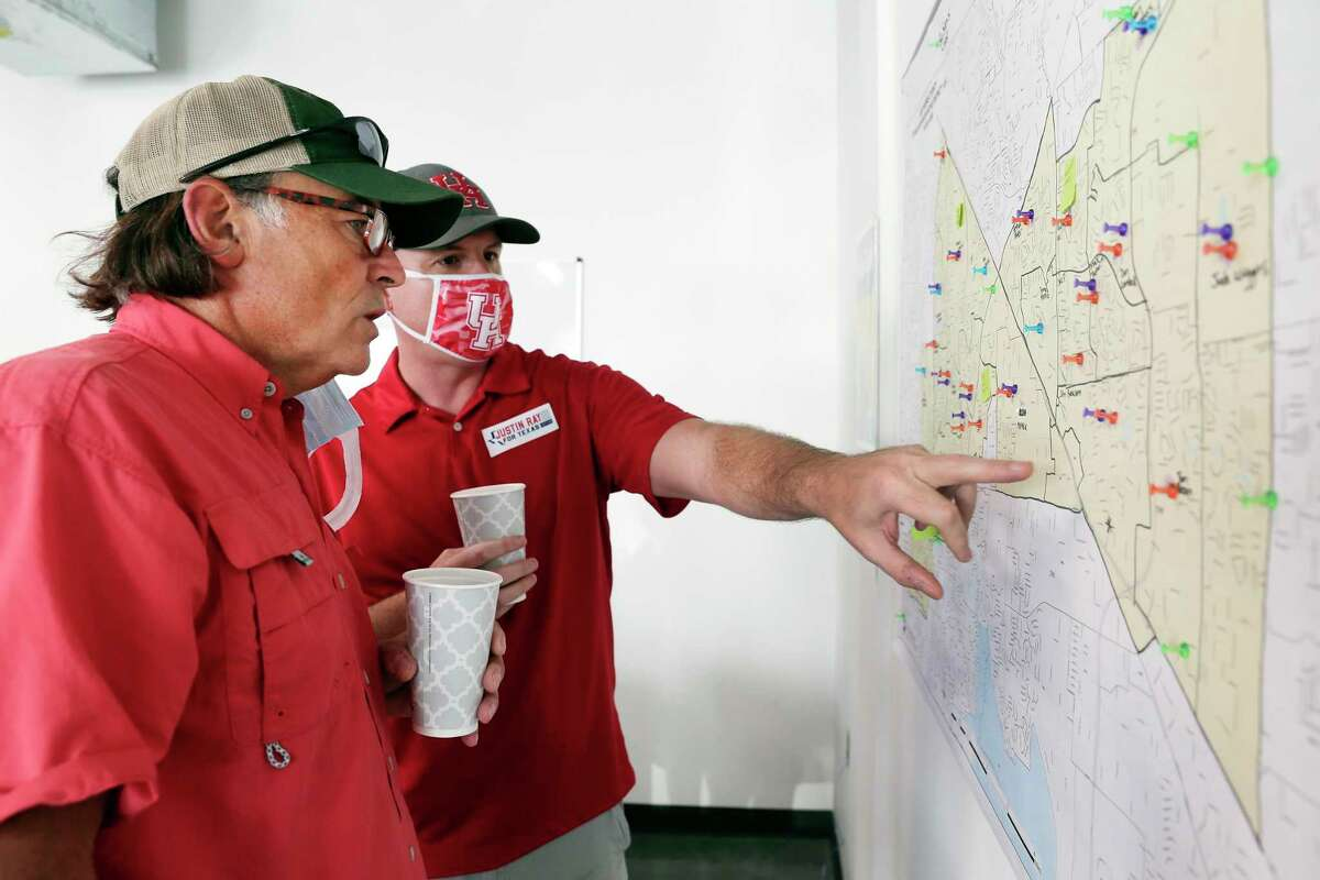 Texas Latino Conservatives political organization founder Orlando Sanchez, left, and candidate Justin Ray, right, go over a map of targeted voters before they and other volunteers walk house-to-house campaigning Ray in a residential subdivision Saturday, Sep. 19, 2020 in Cypress, TX.
