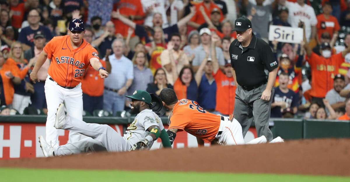 Houston Astros' Jose Siri (26) lands on third base against Oakland Athletics third baseman Josh Harrison after his triple during the first inning of an MLB baseball game at Minute Maid Park, Friday, October 1, 2021, in Houston.
