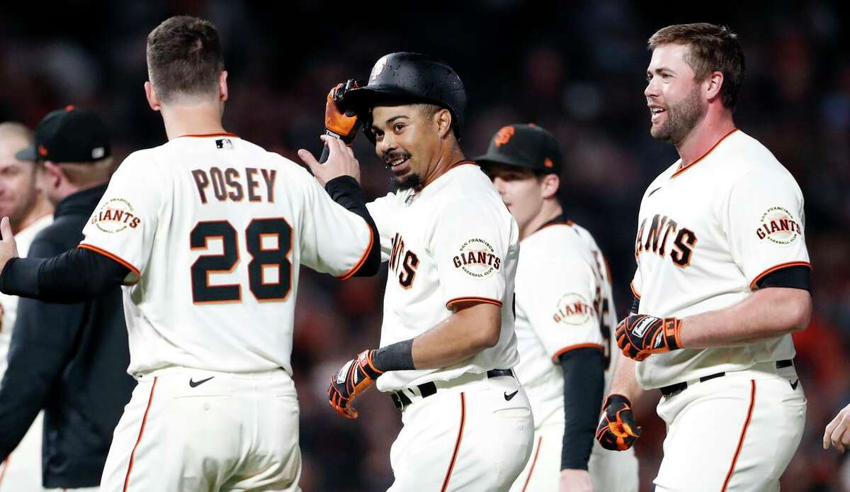 San Francisco Giants' LaMonte Wade, Jr. celebrates his walk off hit with Buster Posey and Darin Ruf after 5-4 win over Arizona Diamondbacks during MLB game at Oracle Park in San Francisco, Calif., on Thursday, September 30, 2021.
