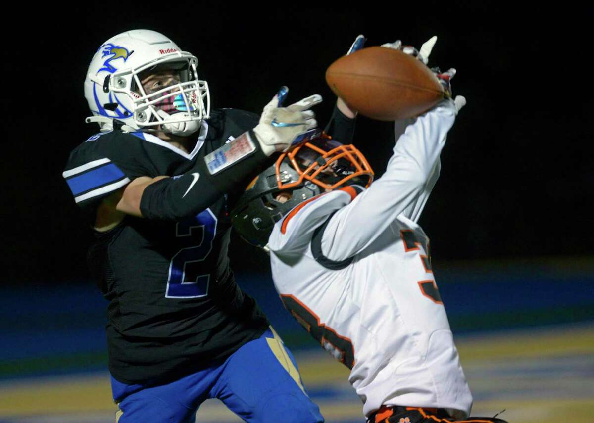 Ridgefield's Matthew Shepard breaks up a pass intended for Newtown's Matt Jacobs during the first half on Friday in Newtown.